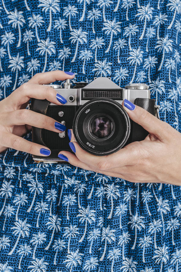 Young Woman Holding a Retro Camera on White Background